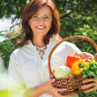 Woman holding basket of vegetables — Stock Photo