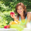 Happy Smiling Young Woman Eating Organic Apple at her Garden — Stock Photo