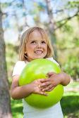 Niña jugando con bola verde en el parque — Foto de Stock