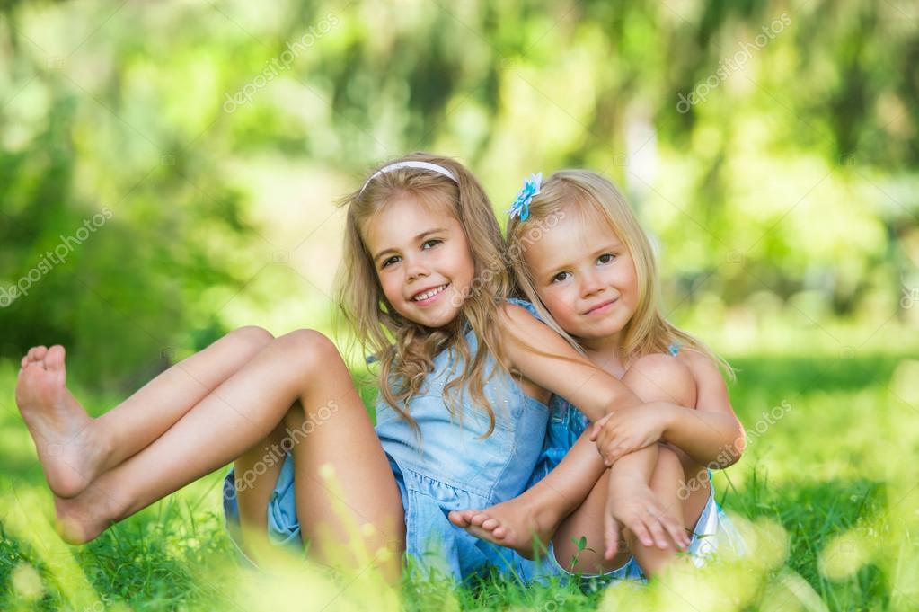 Сладкая блондинка позирует на зеленой лужайке