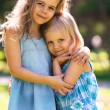 Outdoor portrait of two embracing cute little girls — Stock Photo