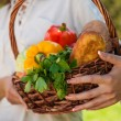 Unrecognizable woman holding basket full of vegetables and bread — Stock Photo #29009951