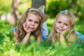 Two little cute girls on lawn in the park — Stock Photo