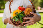 Unrecognizable woman holding basket full of vegetables and bread — Stock Photo
