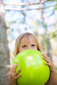 Malá dívka si hraje s zelené koule v parku — Stock fotografie