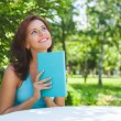 Positive adult woman reading book outdoors — Stock Photo