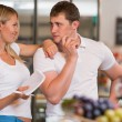 Image of positive couple choosing products in supermarket — Stock Photo #29403797