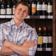 Portrait of confident male with a selection of wines in the back — Stock Photo