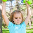 Happy little girl lifting dumbbells in park outdoors — Stock Photo