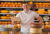 Handsome male owner of a cheese store standing with cheese piece — Stock Photo