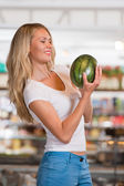 Female customer buying watermelon at supermarket — Stock Photo