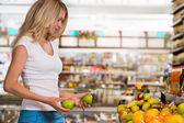 Cute happy brunette shopping in a grocery store — Stock Photo