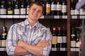 Portrait of confident male with a selection of wines in the back — Stok fotoğraf