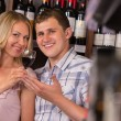 Young couple degustating red wine at supermarket — Stock Photo