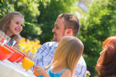 Family eating together outdoors — Stock Photo