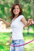 Woman rotates hula hoop on nature background — Stock Photo