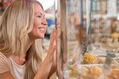 Beautiful young woman standing near supermarket showcase — Stock Photo