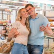 Young couple shopping at supermarket - filling cart — Stock Photo #30392525