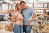 Young couple shopping at supermarket - filling cart — Stock Photo
