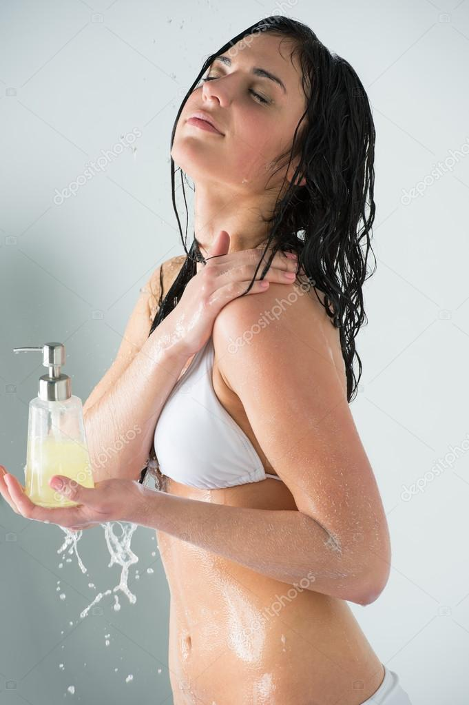 Beautiful Girl Showering Holding Glass Bottle With Shower