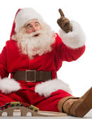 Santa Claus sitting and playing with toys — Stockfoto
