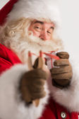 Portrait of happy Santa Claus aiming christmas gift with slingsh — Stock Photo