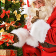 Santa Claus bringing gifts and putting under Christmas tree — Stock Photo