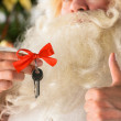Santa Claus holding keys of new house or apartment and thumbs up — Stock Photo #31418081