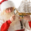 Santa Claus in his workshop making new toys — Stock Photo #31418225