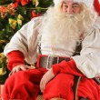Santa Claus sitting in rocking chair near Christmas Tree — Stockfoto