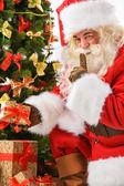 Noel hediyeler getiren ve noel ağacının altında koyarak — Stok fotoğraf