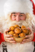 Closeup Santa Claus portrait - holding cookies and looking at ca — Stok fotoğraf