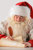 Real Santa Claus writing list of gifts or responding to children — Stock Photo