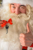 Santa Claus holding keys of new house or apartment and thumbs up — Stock Photo