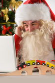 Santa Claus with real beard using laptop — Stockfoto