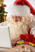Gerçek noel baba sürpriz yüz evde olan dizüstü bilgisayar üzerinde çalışan — Stok fotoğraf