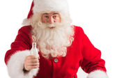 Santa Claus drinking milk from bottle — Stock Photo