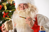 Authentic Santa Claus holding piggy bank and painting it — Stok fotoğraf