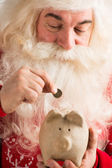 Authentic Santa Claus holding piggy bank and putting golden coin — Stok fotoğraf