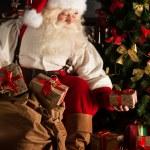 Santa putting gifts under Christmas tree in dark room — Stock Photo
