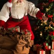 Santa putting gifts under Christmas tree in dark room — Stock Photo