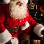 Santa placing gifts under Christmas tree in dark room — Stock Photo
