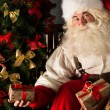 Santa placing gifts under Christmas tree in dark room — Stock Photo #32363073