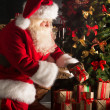 Santa putting gifts under Christmas tree in dark room — Stock Photo #32363231