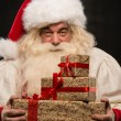 Stock Photo: Santa Claus carrying big stack of Christmas gifts