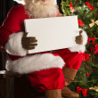 Santa Claus sitting indoors at dark room near Christmas tree and — Stock Photo #32363607