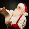 Portrait of happy Santa Claus reading Christmas letter — Stock Photo