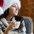 Beautiful young woman wearing Santa Claus red hat sitting at cafe — Stok fotoğraf