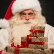 Santa Claus carrying big stack of Christmas gifts — Stock Photo