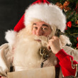 Santa Claus calling with vintage phone while reading an old roll — Stock Photo